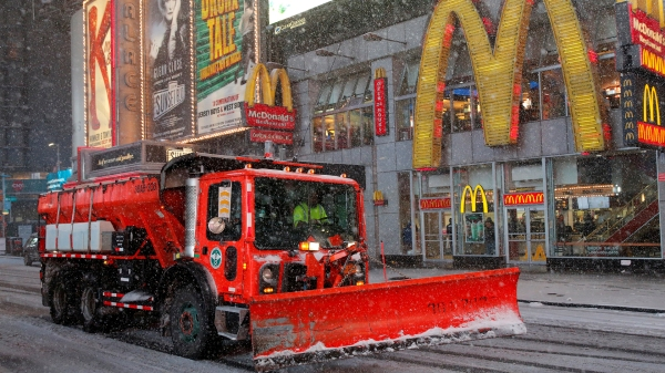A snow plow drives through Times Square as snow falls in Manhattan, New York